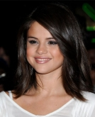 Selena Gomez's Soft Brunette Hairstyle with Side-Swept Bangs